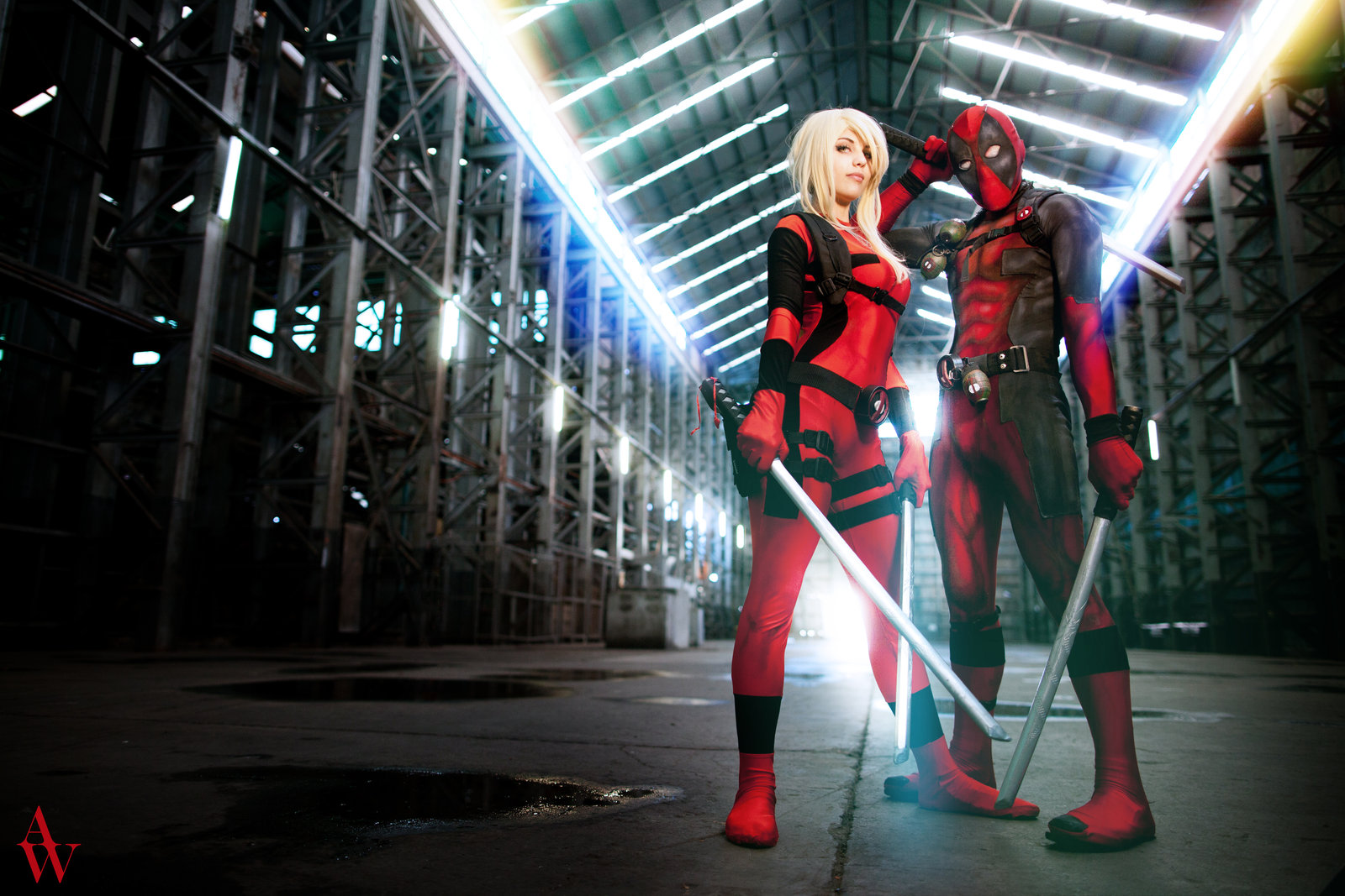 Two deadpool cosplayers taken against a warehouse background